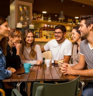 A group of friends talking and drinking coffee at the cafe
